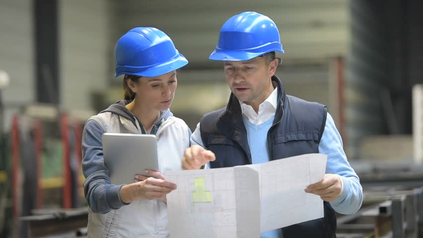 two-people-reviewing-plans-in-factory