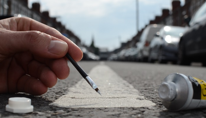 Hand painting a street stripe